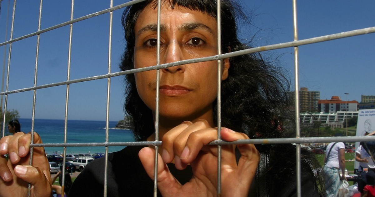 Australian artist Mireille Astore who fled Beirut during the 1975 war and arrived in Australia as a migrant stands in a barbed wire cage to draw attention to Australia's mandatory detention policy on Dec. 13, 2003.</p>