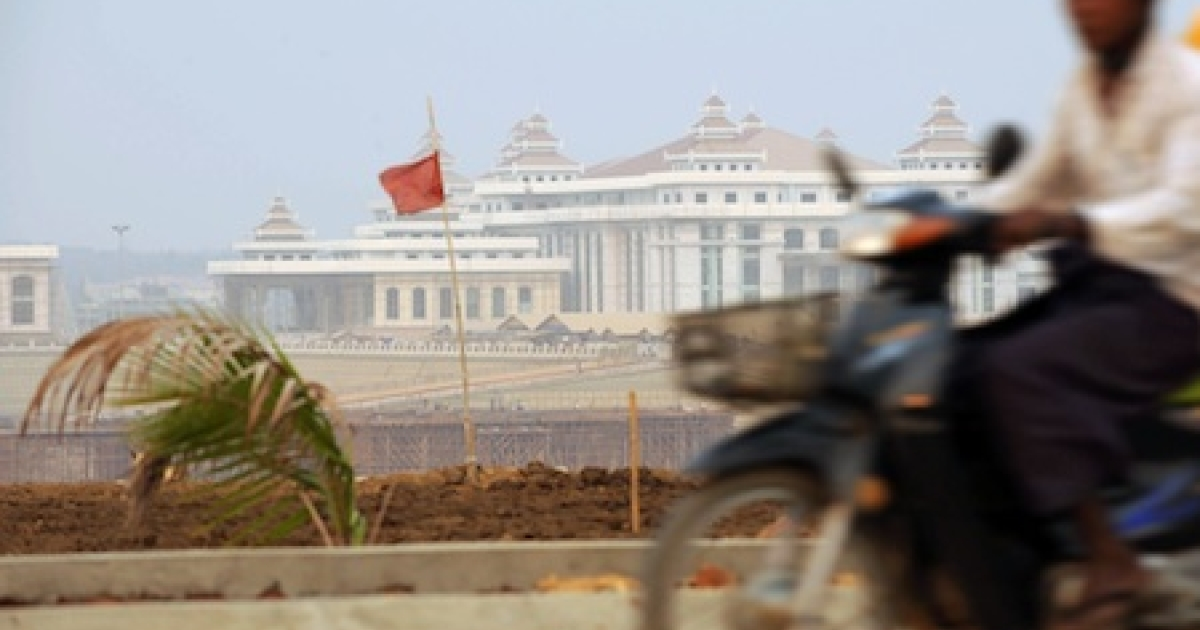 Photo taken on March 26, 2010 shows a Myanmar man riding his motorcycle past the construction site of the country's new parliament building in Naypyidaw.</p>