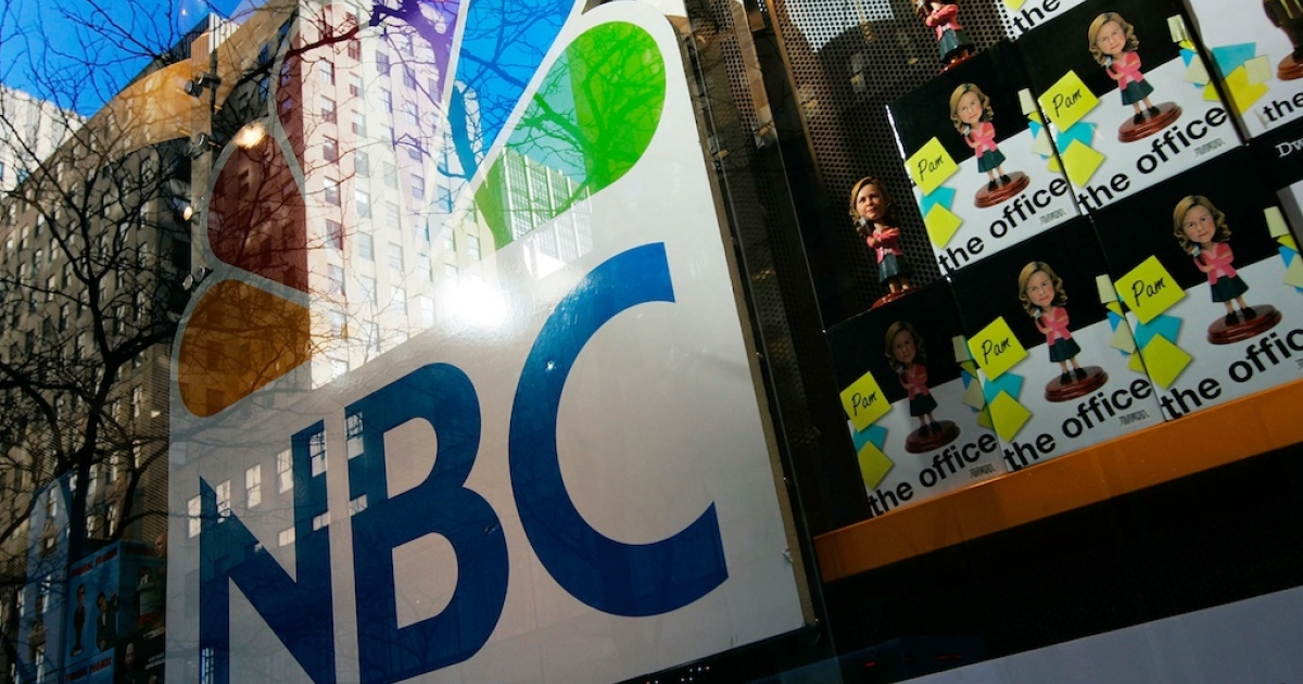 An NBC store is seen through a window reflecting Rockefeller Center.</p>