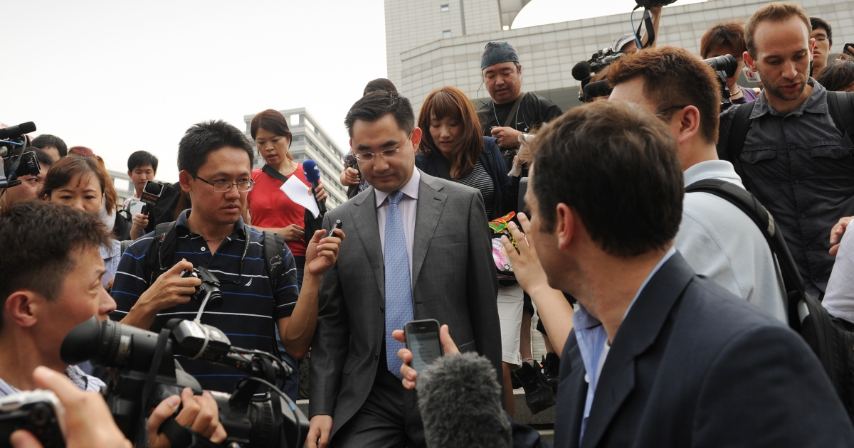 Reporters surround He Zhengsheng, a lawyer for Neil Heywood's family, as he leaves the Intermediate People's Court in Hefei, Anhui, China, on Aug. 20, 2012.</p>