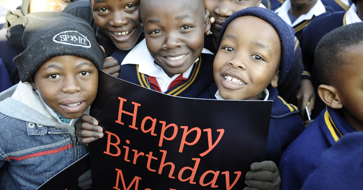 South African schoolchildren hold signs as they prepare to sing happy birthday to former South African President Nelson Mandela, on his 94th birthday, at Batsogile Primary School in Soweto, on July 18, 2012. The nation's 12 million schoolchildren began their day with a special birthday song, ringing with the line: