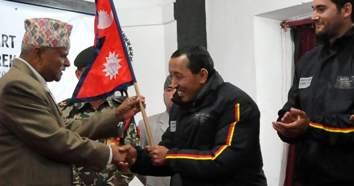 Nepal's President Ram Baran Yadav (L) hands over the country's national flag to Nepalese climber Apa Sherpa (2R) who holds the record for the number of times he has summitted Mount Everest, flanked by his team members at the President's Office in Kathmandu on January 12, 2012. On January 15, Apa and his team will begin their trek on the 1700 kilometre, 120 days trek dubbed 'Great Himalayan Trail' to highlight the impacts of climate change.</p>