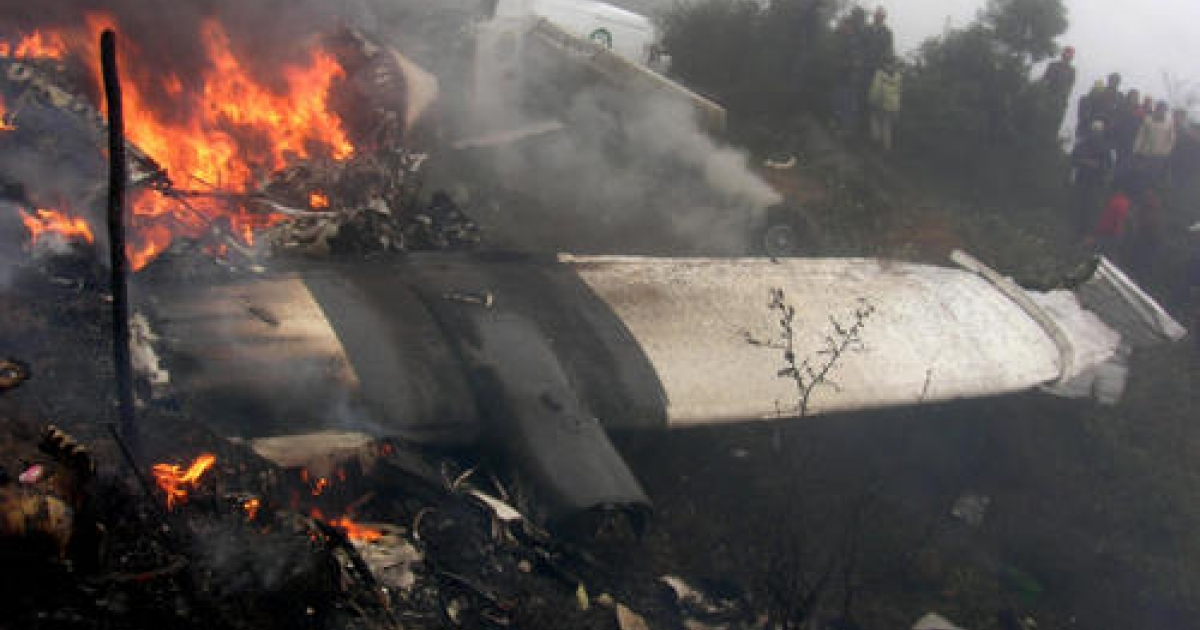 In this picture taken on October 9, 2008, bystanders look on as the wreckage of a Yeti Airlines aircraft burns at the airport in Lukla.  Mistakes by the crew of a plane that crashed in Nepal's Everest region caused the accident which killed 18 people, officials said January 1, 2009, as a report into the accident was released. Fifteen people including 13 Indian tourists were killed when an aircraft with 21 people on board crashed at Jomsom airport in north-central Nepal on Monday morning.</p>