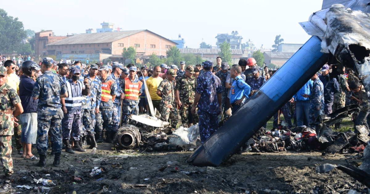 Nepalese rescue team members looks at the remains of a Sita air plane after it crashed in Manohara, Bhaktapur on the outskirts of Kathmandu on September 28, 2012.</p>