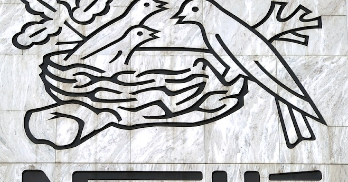 A crow flies above a Nestle sign at the company's headquarters in Vevey, Switzerland.</p>