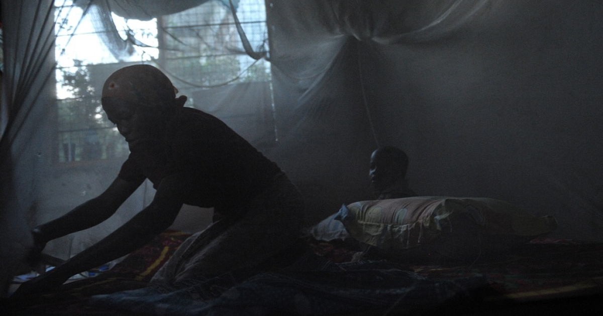 A mother and child sit under a mosquito net in Tanzania, one of the countries where the pioneering RTS,S vaccine was tested.</p>