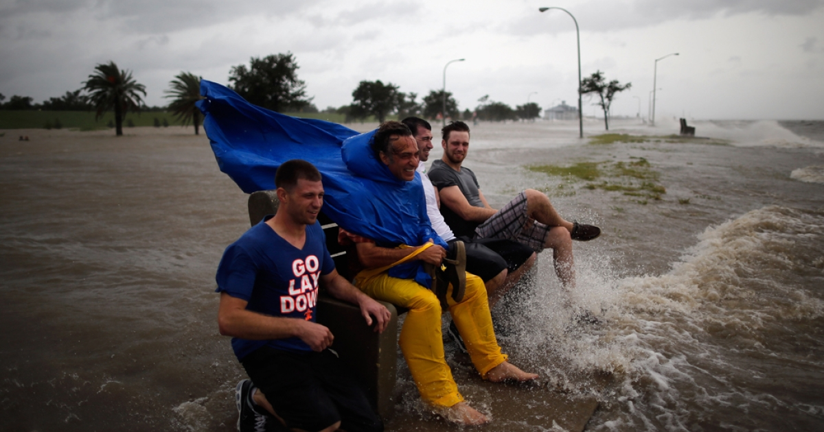 A group of men sit on a bench at the edge of Lake Pontchatrain as Hurricane Isaac approaches on August 28, 2012 in New Orleans, Louisiana.</p>