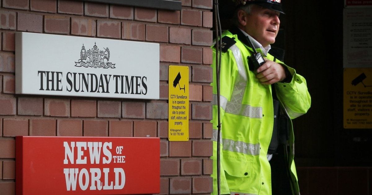 A policeman walks through the security gates at News International's plant in London, on July 7, 2011.</p>
