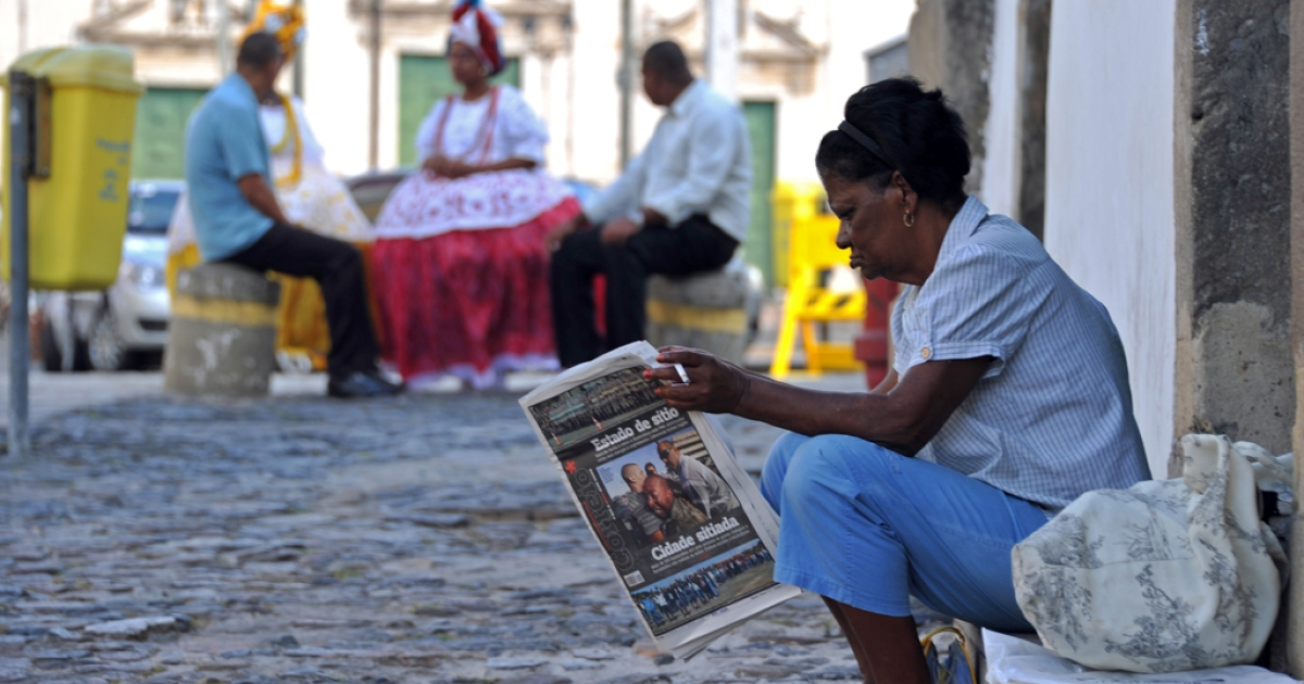 A woman reads a newspaper in Salvador, Bahia, Brazil.</p>