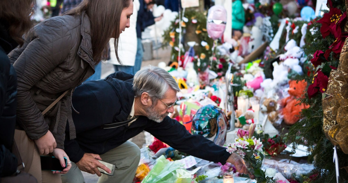 A man lays flowers at a memorial on December 24, 2012 for those killed in the shooting at Sandy Hook Elementary School in Newtown, Connecticut.</p>