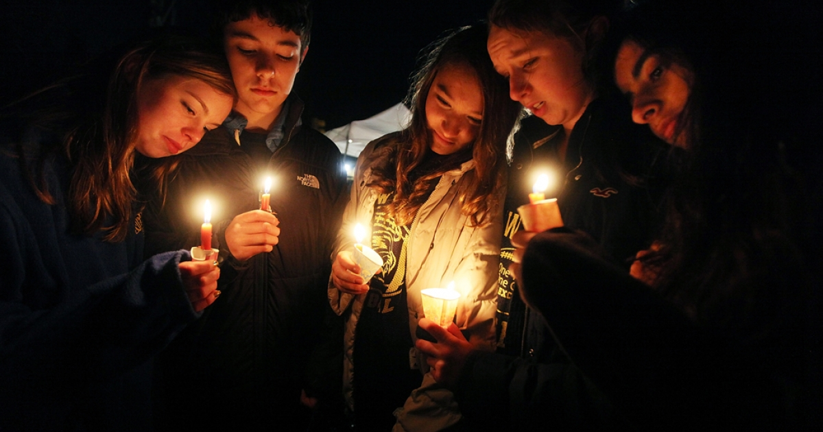 Newtown, Conn. residents Claire Swanson, Ian Fuchs, Kate Suba, Jaden Albrecht and Simran Chand hold candles at a memorial for victims on Sunday, following the mass shooting at Sandy Hook Elementary School on Dec. 16, 2012 in Newtown, Connecticut.</p>
