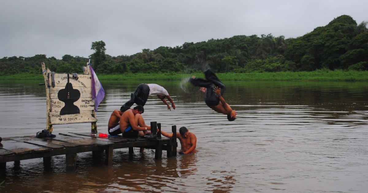 Nicaraguan kids take turns jumping in the water at a camp for Sandinista youths built in an area disputed by Costa Rica.</p>