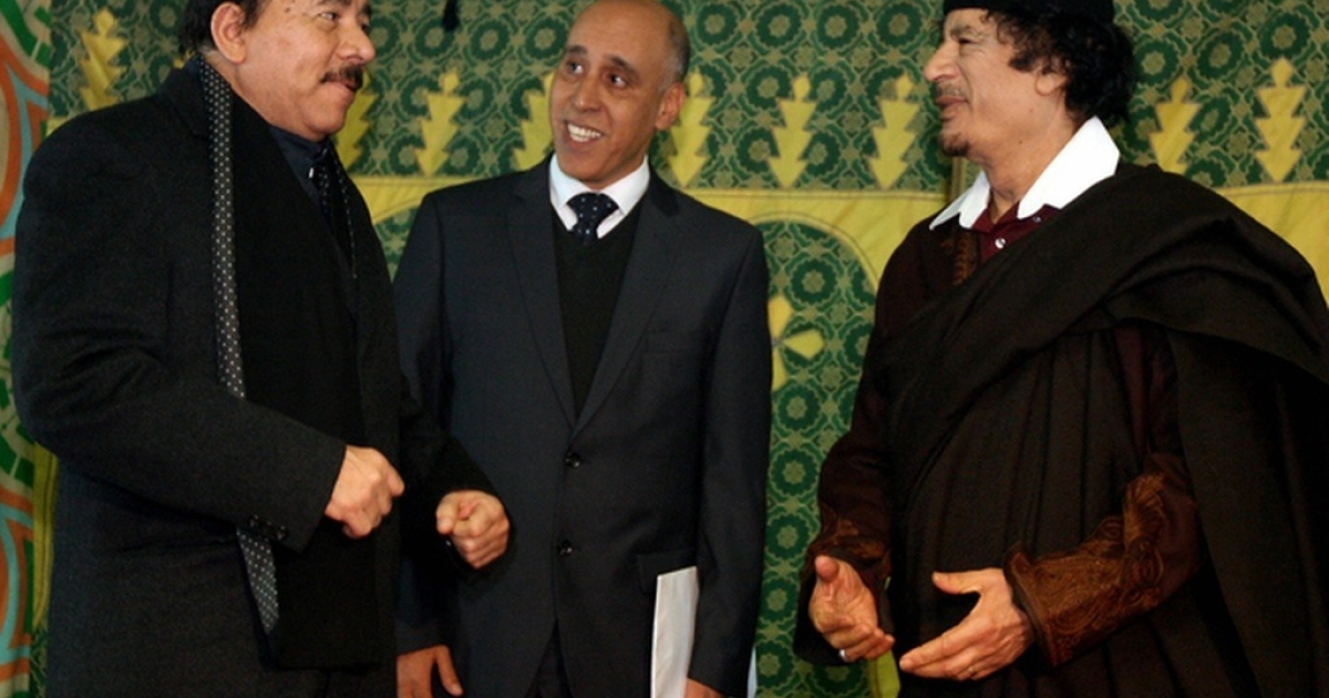 Ortega (far left) standing with his man, Gaddafi</p>