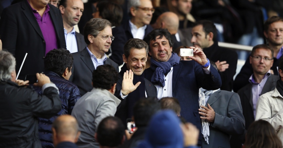 Former French president Nicolas Sarkozy smiles as he leaves the stand during the French L1 football match Paris vs Sochaux on September 29, 2012 at the Parc des Princes stadium in Paris.</p>