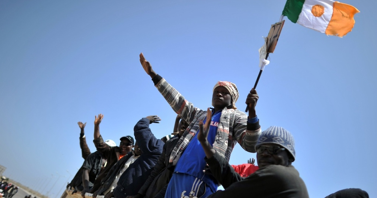 An African migrant holds the flag of Niger as he and others ride in trucks on their way to be evacuated from Libya by an International Organization for Migration (IOM) ship.</p>