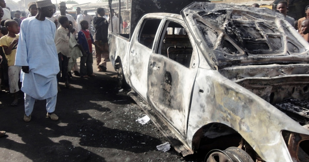 A resident inspects a police patrol van outside Sheka police station in the northern Nigerian city of Kano on January 25, 2012. The van was burnt in bomb and shooting attacks on the police station the previous night by around 30 members of Boko Haram Islamist group, wounding a policeman and killing a female visitor, according to residents.</p>