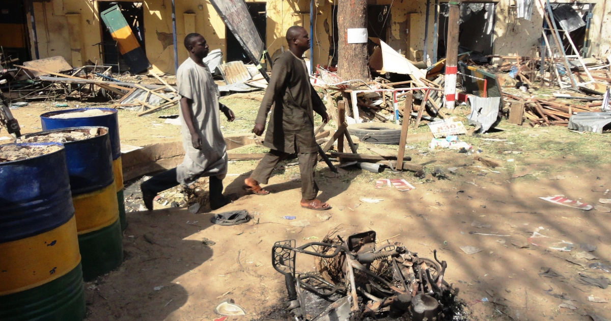 Two residents pass by bombed corner shops attached to Bompai police barracks in the northern Nigerian city of Kano on January 24, after multiple explosions and gun assaults by Boko Haram in the city killed at least 185 people.</p>