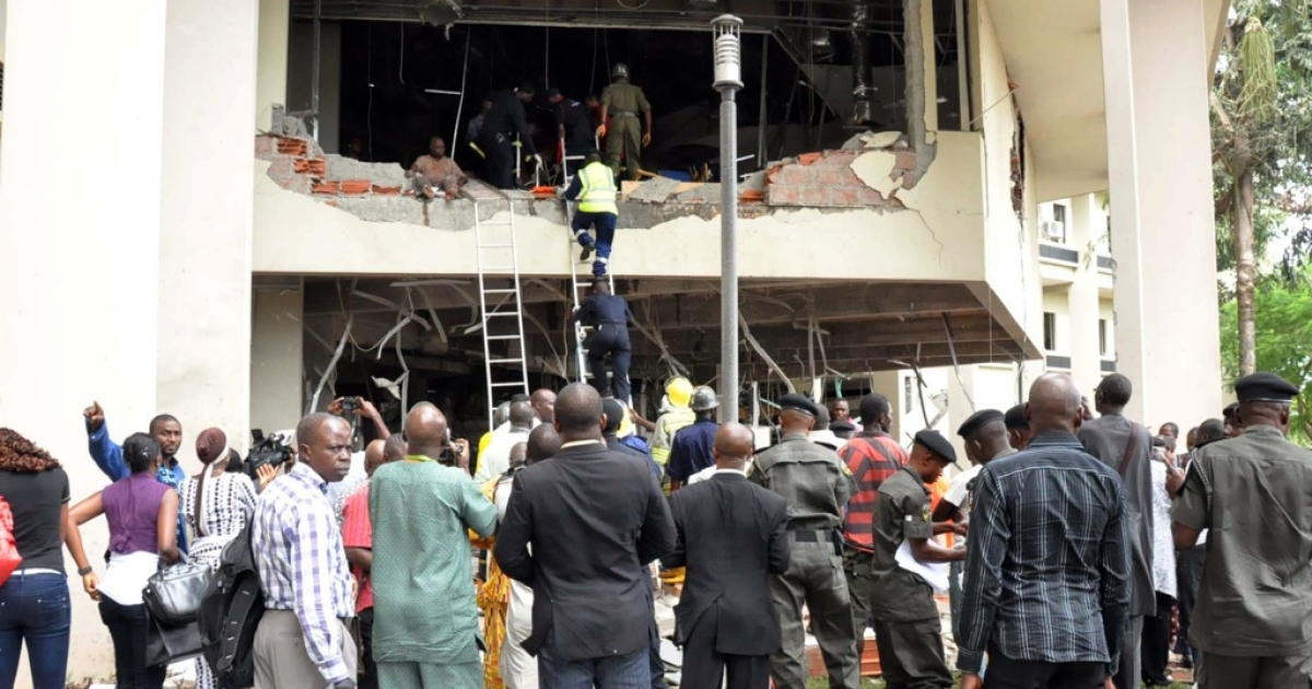 Nigerians look at rescue teams working in the debris of the United Nations House in Abuja on August 26, 2011 after it was hit by a bomb that killed at least 18 people, leaving others trapped and causing heavy damage. Witnesses reported that the bomb exploded after a suspect rammed a car through the front gate. Parts of the first two floors of the building were blown out and rescue workers scrambled to rescue those left inside.</p>