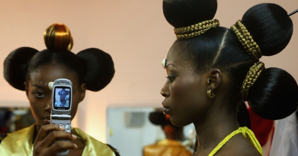 Nigerian fashion models Mary Jane Unueroh and Fome Emede, left, take a photo of themselves with a cell phone.</p>