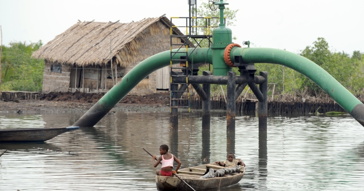 Nigeria's Niger Delta area is the center of the country's oil production and has been hit by protests by local people against pollution of the environment and lack of development and jobs for local communities. Here Nigerian children boat past an oil pipeline head near their home at Andoni settlement, Bonny waterways in Rivers State on April 12, 2011.</p>