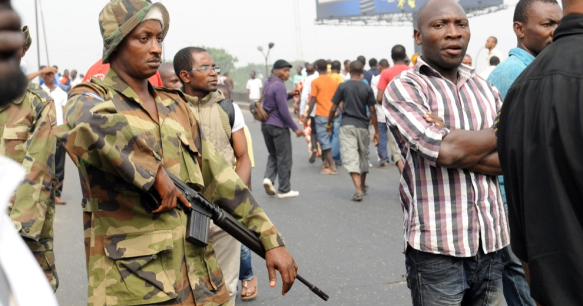 A soldier stands next to protesters at Ojota district in Lagos on Jan. 16, 2012. Nigerian security forces fired tear gas and shot into the air Monday to disperse around 300 protesters in Lagos as authorities moved to prevent demonstrations in various parts of the country. Nigerian unions announced on Jan. 16 they were suspending a week-old nationwide strike over fuel prices which has shut down Africa's most populous nation and brought tens of thousands out in protest.</p>