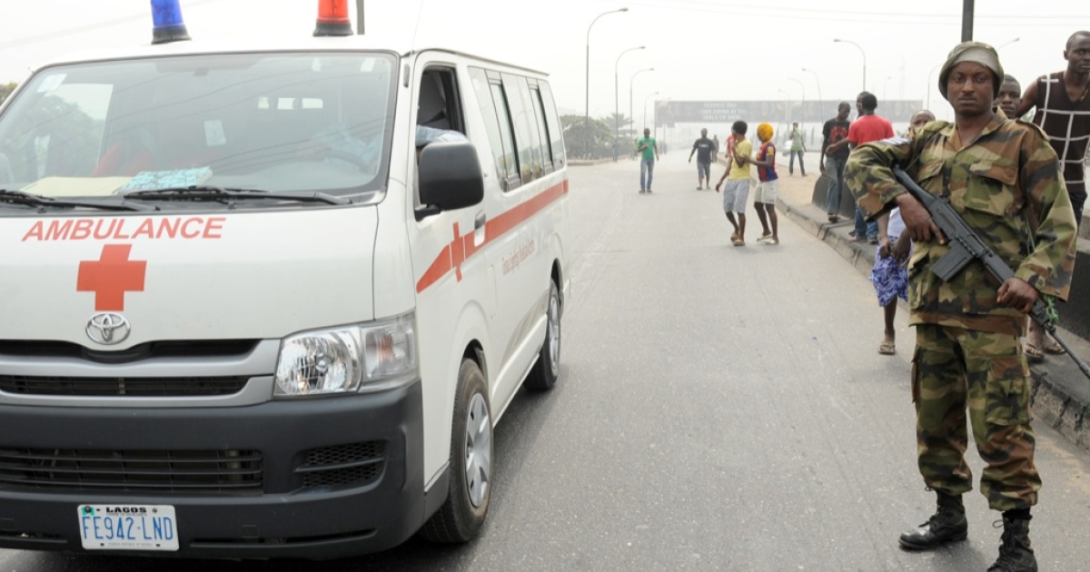 An ambulance drives past a soldier standing away from protesters at Ojota district in Lagos on Jan. 16, 2012. Soldiers have been deployed in some parts of Lagos at main protest sites.</p>