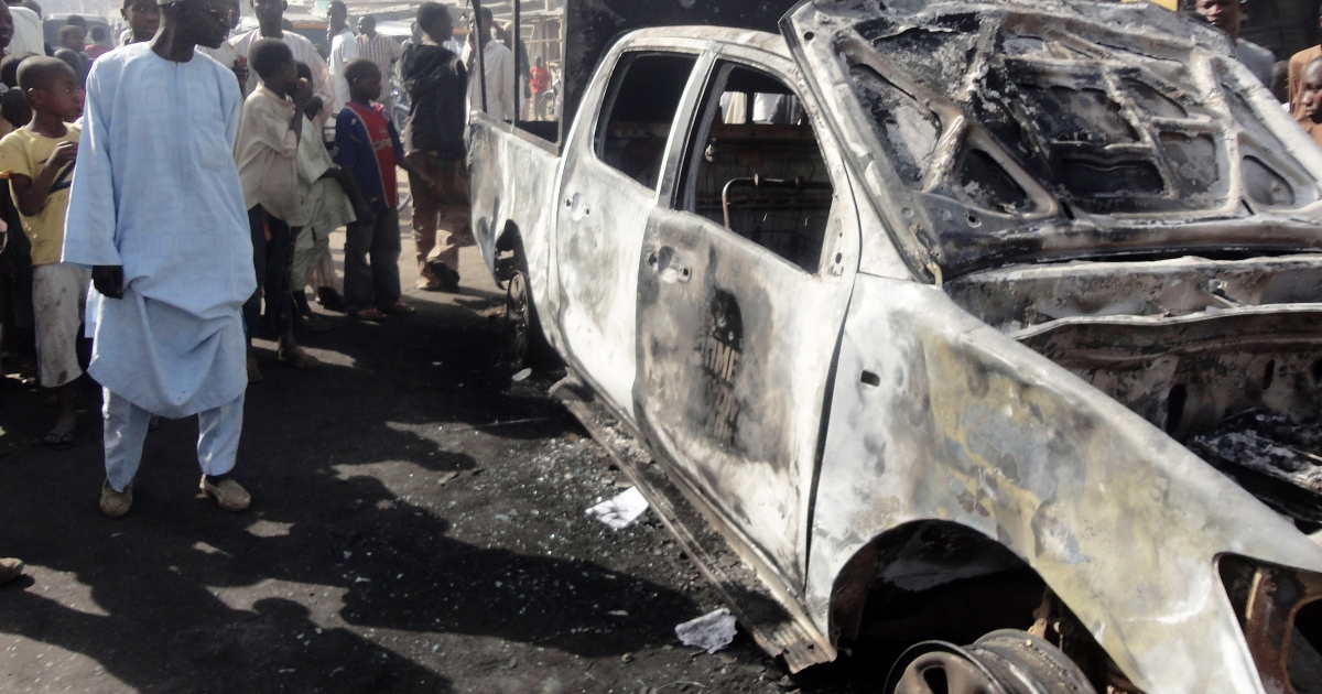 A resident inspects a police van outside a police station in the northern Nigerian city of Kano on January 25, 2012. The van was burnt in  attacks on the police station the previous night by around 30 members of Boko Haram militants, wounding a policeman and killing a female visitor, according to residents.</p>