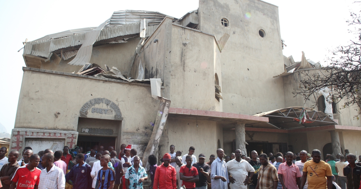 People stand in front of the partially destroyed St. Theresa Catholic Church after a bomb blast in the Madala Zuba district of Nigeria's capital Abuja on December 25, 2011.  Islamist militant group Boko Haram claimed responsibility for church bombings that killed dozens of people in Nigeria that day.</p>