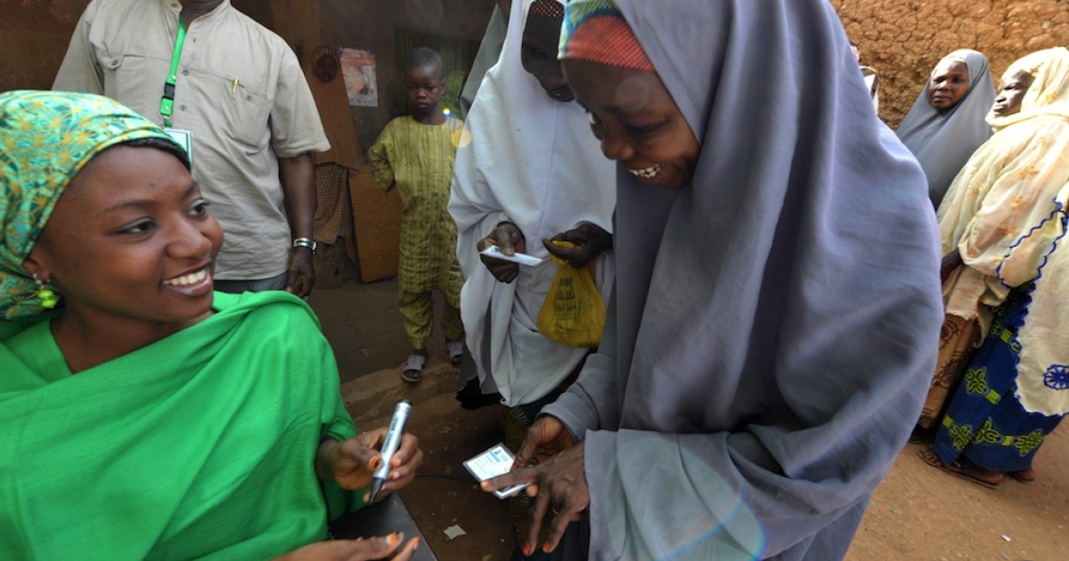 An electoral worker marks the finger of a Nigerian woman at a polling station during the presidential elections in Daura on April 16, 2011.</p>
