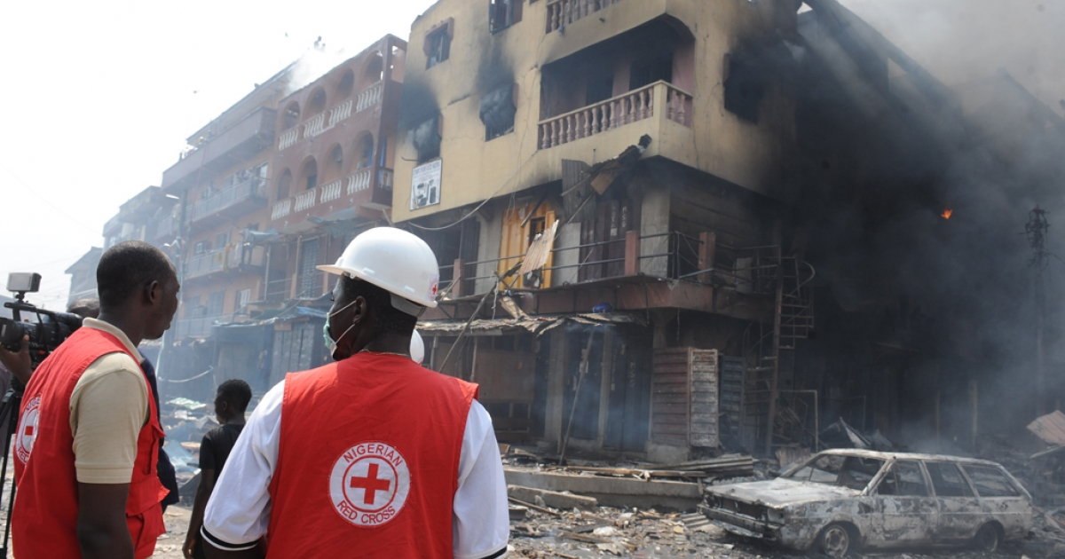 Red Cross officials look at a building on fire after a heavy explosion on December 26, 2012 in Lagos. Fire ripped through a crowded neighborhood in Nigeria's largest city and wounded at least 30 people after a huge explosion rocked a building believed to be storing fireworks, officials said.</p>