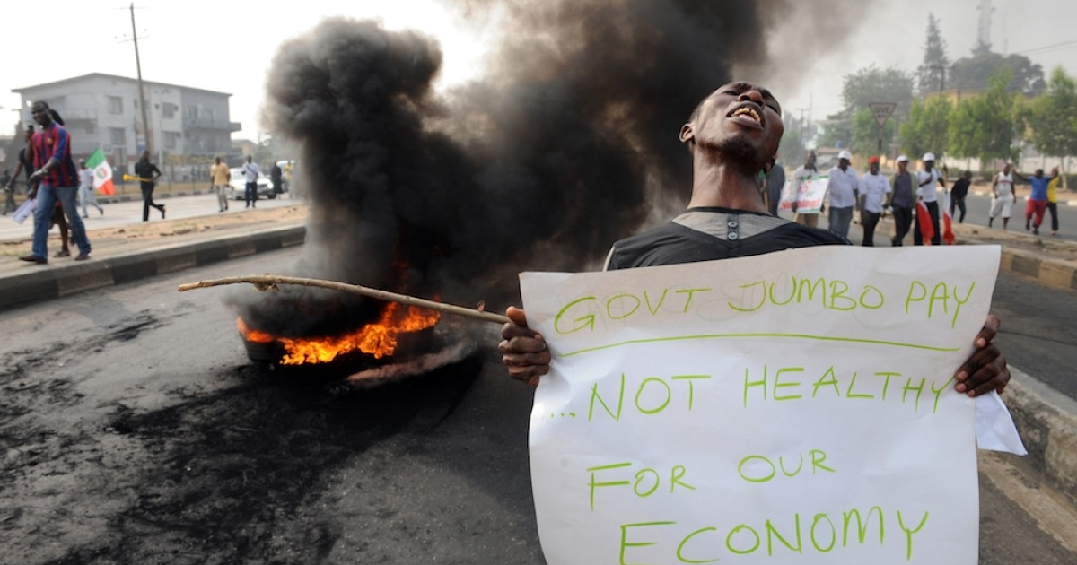 A man carries a placard beside a bonfire during a demonstration against soaring petrol prices following government's decision to abolish decades—old fuel subsidies, on January 9, 2012 in Lagos. One protester was shot dead in Nigeria's commercial capital Lagos during the national strike over fuel prices, a union leader said.</p>