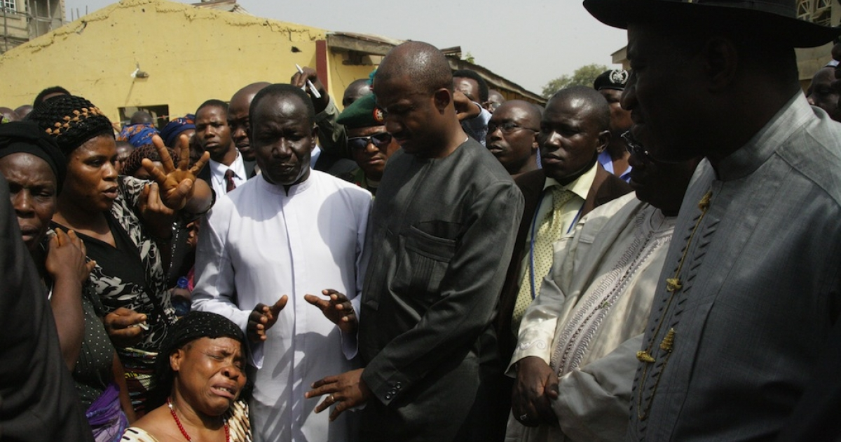 Nigerian President Goodluck Jonathan (R) listens to relatives of Christmas bomb blast's victims as he visits the damaged St. Theresa Catholic Church in Madalla near the capital Abuja on December 31, 2011.</p>