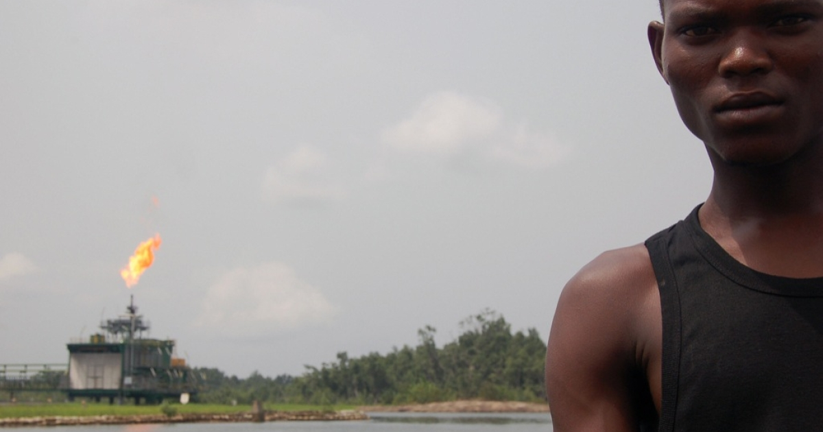 An ethnic Ijaw boatman steers past the energy giant Shell's Egwa oil flow station in the Niger Delta, Nigeria, February 2006. Ijaw rebels had attacked several Shell facilities in the delta, cutting Nigeria's oil exports by more than eight percent.</p>