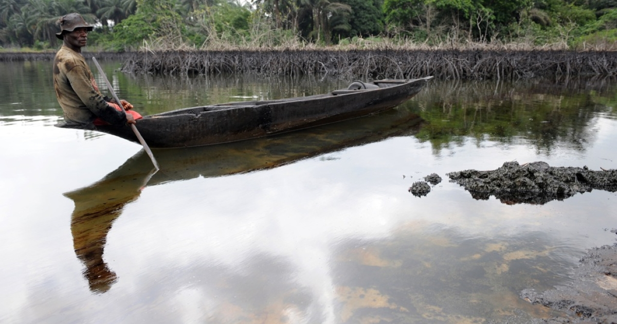 Gaagaa Gidom, a 60-year-old fisherman and father of eight, looks at the spilled crude oil floating in the waters of the Niger Delta swamps of Bodo, a village in the famous Nigerian oil-producing Ogoniland, which hosts the Shell Petroleum Development Company on June 24, 2010.</p>
