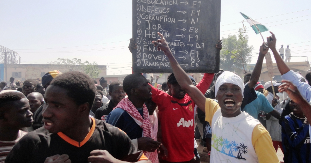 A protester carries a placard against poor social services in the northern Nigerian city of Kano, on January 11, 2012. Hundreds of thousands of protesters took to the streets for a week, demonstrating against the ending of subsidy that doubled and tripled the price of fuel.</p>