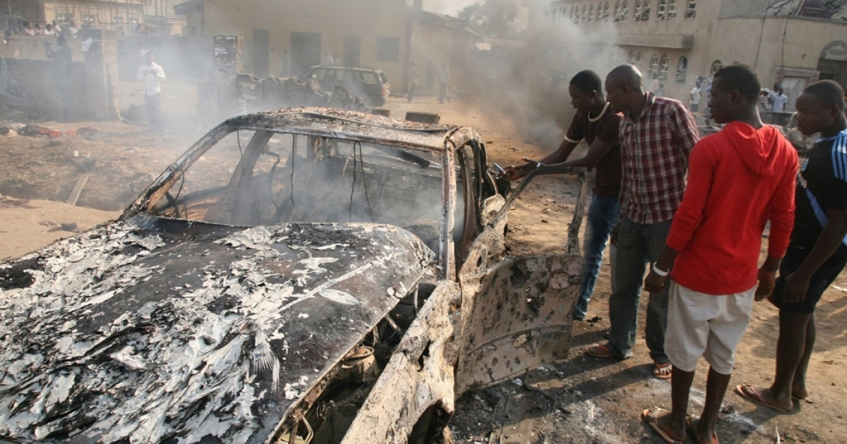 Nigerians look at the wreckage of a car following a bomb blast at St Theresa Catholic Church outside the Nigerian capital Abuja on December 25, 2011. Two explosions near churches during Christmas Day services in Nigeria, including one outside the country's capital, killed at least 28 people amid spiralling violence blamed on an Islamist extremist group, Boko Haram.</p>