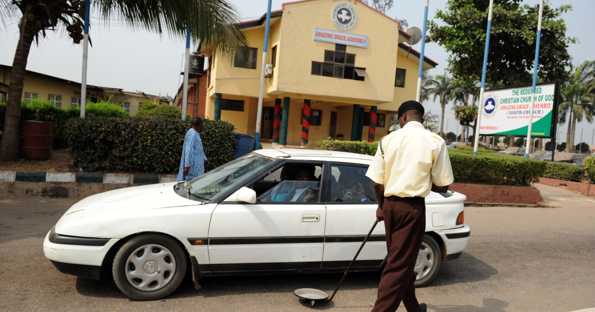 A security guard uses a bomb detector to scan underneath a car at the main gate to the Redeemed Christian Church of God.</p>