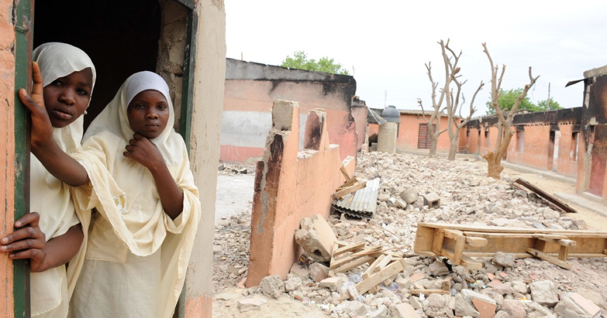Female student stands in a burnt classroom at Maiduguri Experimental School, a private nursery, primary and secondary school burnt by the Islamist group Boko Haram to keep children away from school in Maiduguri, northeastern Nigeria on May 12, 2012.</p>