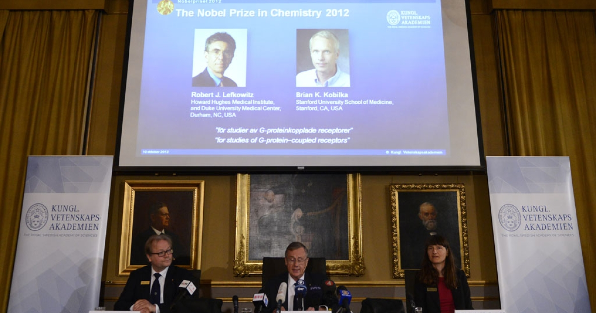 Pictures of US scientists Robert Lefkowitz, above left, and Brian Kobilka are shown as winners of the 2012 Nobel Prize in Chemistry by Staffan Normark, center, permanent secretary of the Royal Swedish Academy of Sciences on October 10, 2012 in Stockholm.</p>