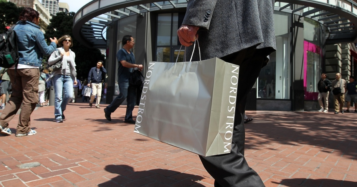 A shopper carries a Nordstrom bag as he walks along Market Street in San Francisco, Calif.</p>