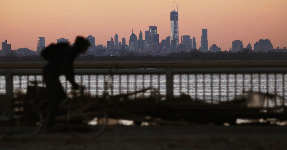 A man bikes past debris in the Rockaway neighborhood with the Manhattan skyline in the distance on November 6, 2012 in the Queens borough of New York City. The Rockaway section of Queens was one of the hardest hit areas. Many voters in New York and New Jersey are voting at alternate locations in the presidential election due to disruption from Superstorm Sandy as a Nor'easter storm approaches.</p>
