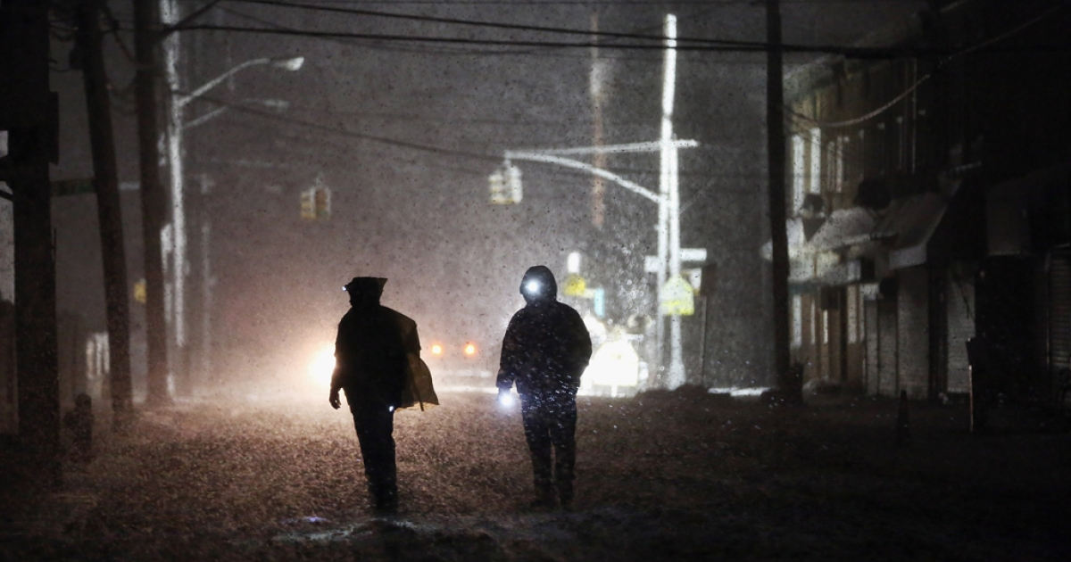 People walk through a darkened street using flashlights as a police spotlight shines behind them during a Nor'Easter snowstorm in the Rockaway neighborhood on November 7, 2012 in the Queens borough of New York City. The Rockaway Peninsula was especially hard hit by Superstorm Sandy and some are evacuating ahead of the coming storm.</p>