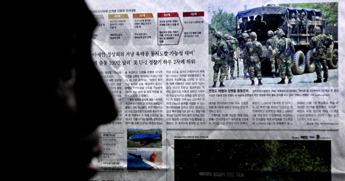 A man reads a newspaper report about a North Korea missile test and the training of South Korean troops in Seoul on May 29, 2009.</p>