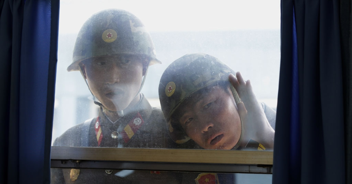 North Korean soldiers look in from outside the U.N. Command Military Armistice Commission meeting room at the border village of Panmunjom in the Demilitarized Zone (DMZ) that separates the two Koreas since the Korean War, in Paju, north of Seoul, on April 24, 2011.</p>