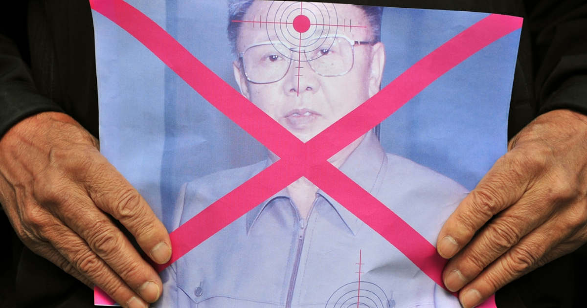 A South Korean protester holds a portrait of North Korean leader Kim Jong Il during a rally in central Seoul on March 25, 2011.</p>
