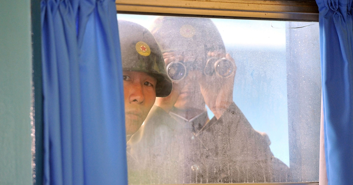 North Korean soldiers look in from outside the UN Command Military Armistice Commission meeting room on July 15, 2011 in Panmunjom, South Korea.</p>