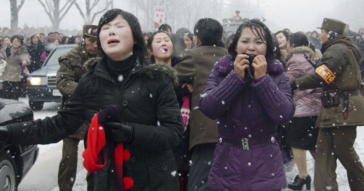 Mourners react as a car carrying Kim Jong Il's body passes by during the funeral procession in Pyongyang. In a New Year message, North Korea called on the country to defend the new leader, Kim Jong Un, to the death, and to be prepared to act as