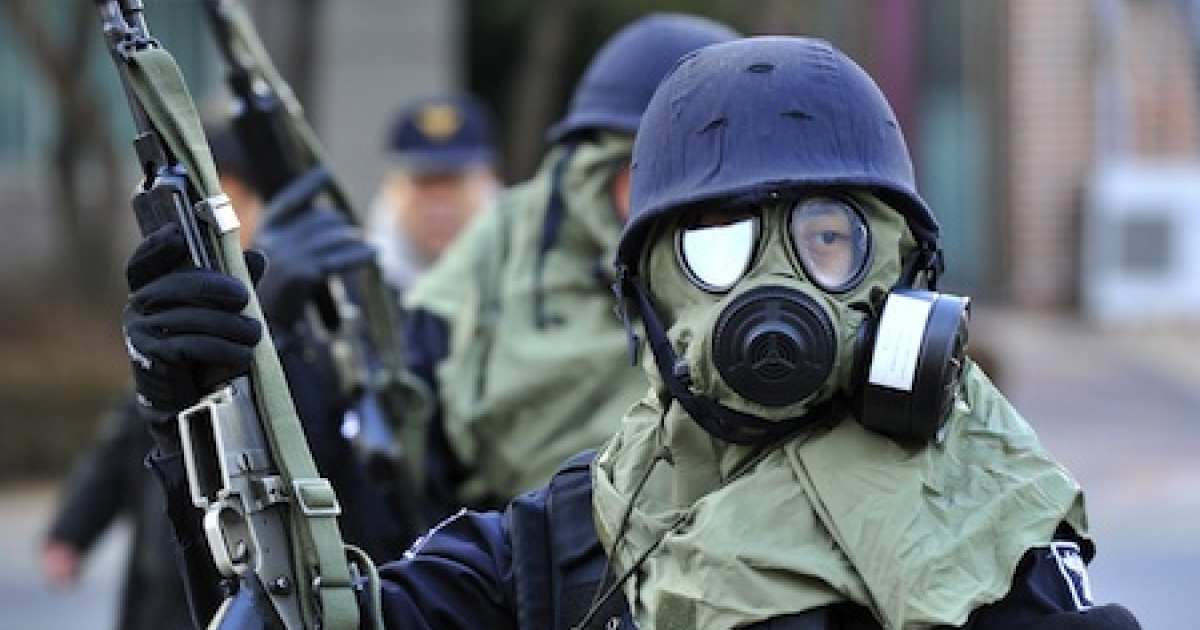 South Korean policemen wearing gas masks stand guard during a civil defence drill at an apartment village in Paju near the Demilitarized Zone (DMZ) separating the two Koreas on December 15, 2010. South Korea launched its biggest-ever civil defence drill amid high tensions over North Korea's deadly artillery attack last month and its nuclear programs.</p>