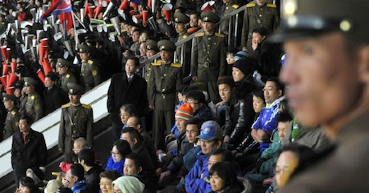 North Korean security personnel stand guard around Japanese supporters (in blue), while North Korean supporters cheer for their team behind them during the World Cup 2014 qualifying match in Pyongyang on November 15, 2011. Japan was defeated by North Korea 0-1.</p>