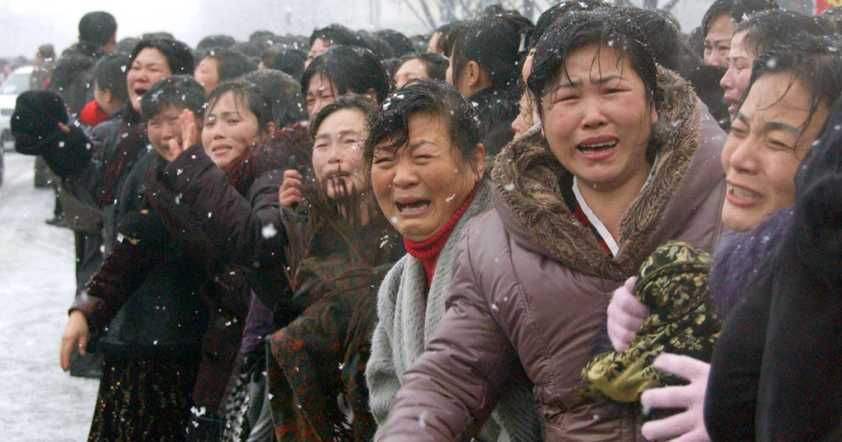 In this photo taken on December 28, 2011 mourners react as a car Kim Jong-Il's body passes by during the funeral procession in Pyongyang.         AFP PHOTO / KYODO</p>